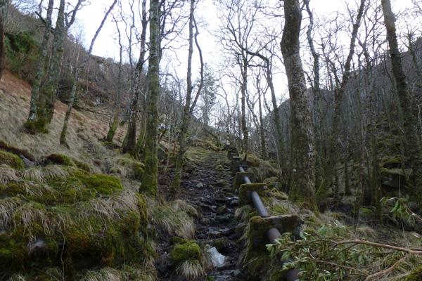 Path by metal pipeline ascending to dammed lochan