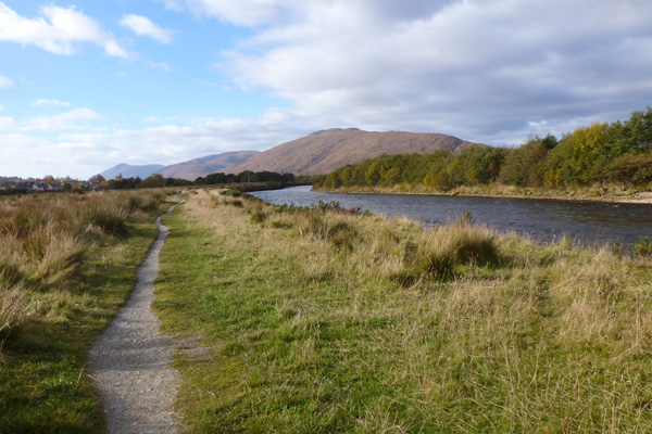 The path across rough meadow by River Lochy