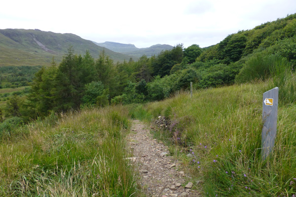 The path turns left for a steepish descent to the valley bottom