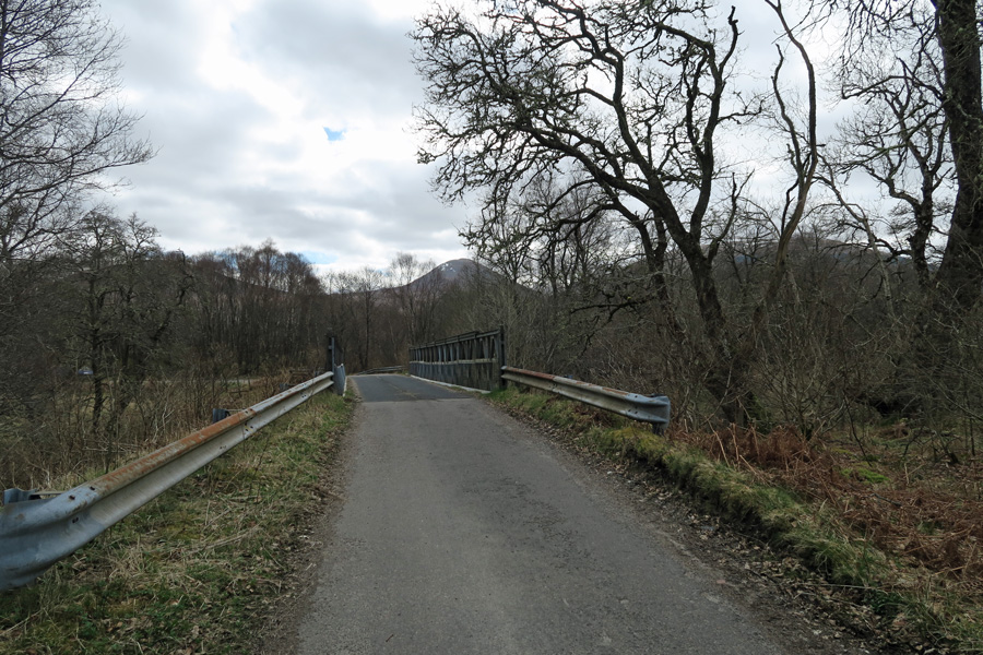 Park by the large metal bridge